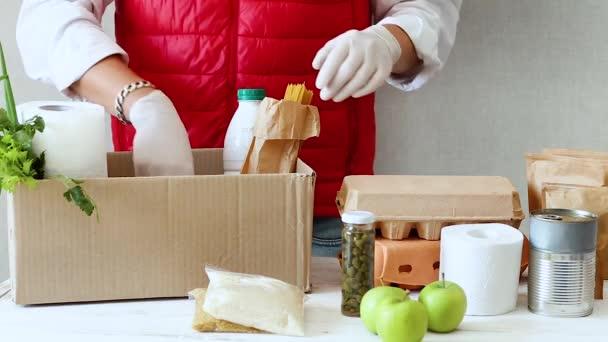 Freiwillige in Schutzmaske und Handschuhen legen Lebensmittel in die Spendenbox. Liefermann-Mitarbeiter in roter Weste packt Karton mit Lebensmitteln. Service Quarantäne-Pandemie Coronavirus.