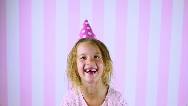 Malá blondýnka čeká na překvapení, usmívá se v narozeninové růžové čepici Dítě slaví své narozeniny doma. Všechno nejlepší.