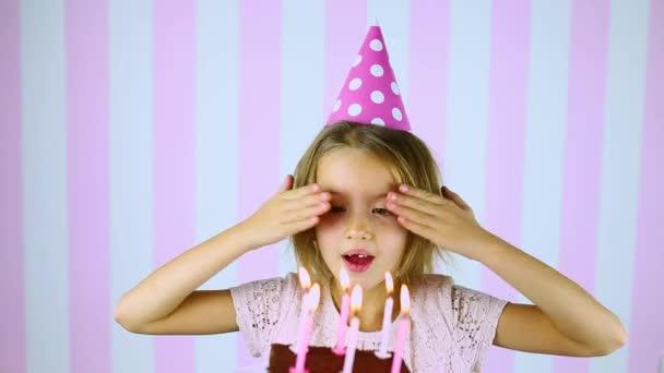 Boldog meglepetés, csukott szemmel, rózsaszín sapkás kislány gyertyákat fúj el egy szülinapi tortán.