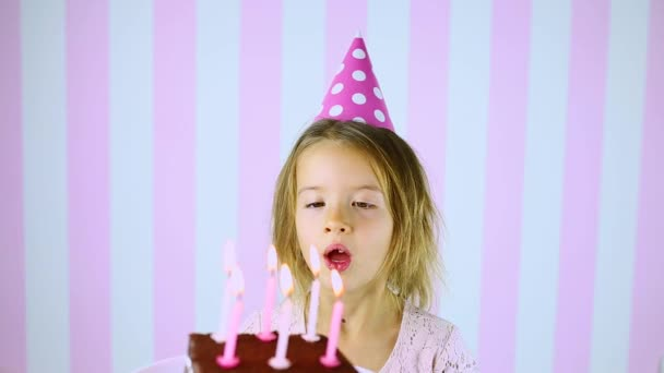Šťastné překvapení, zavřené oči holčička v růžové čepici sfouknutí svíčky na narozeninový dort