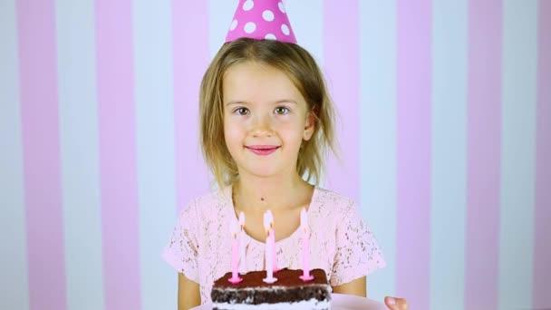 Kis szőke lány mosolyog szülinapi rózsaszín sapkában, egy torta gyertyákkal a kezében.