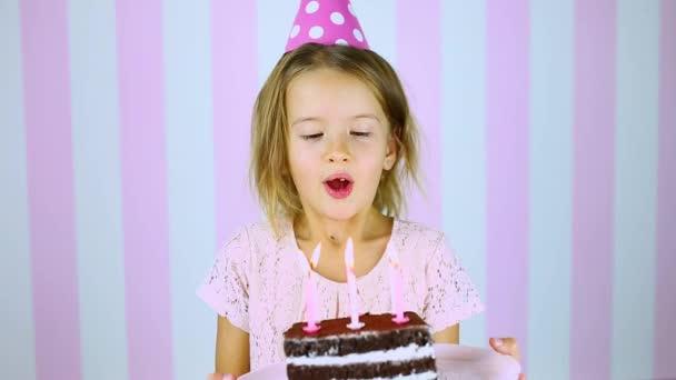 Šťastná a usmívající se holčička v růžové čepici sfouknutí svíčky na narozeninovém dortu