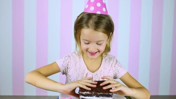 Šťastná a usmívající se holčička v růžové čepici jíst narozeninový čokoládový dort