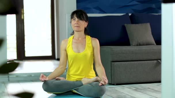 Seniorin mit schlanker Körperform in Sportbekleidung sitzt zu Hause in Pose auf Yogamatte.