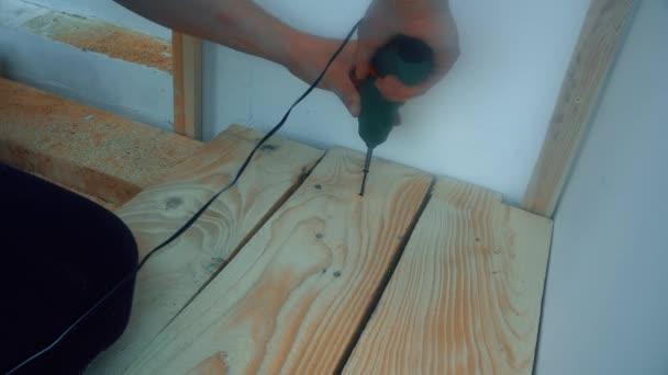mužských rukou Otočením šroubu do dřevěné desky sílu šroubovákem