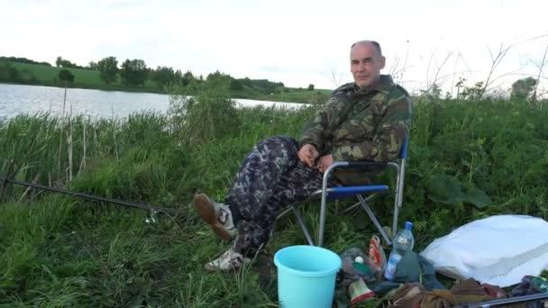 Kursk, Oroszország - 2017. május 28.: Halász ül egy horgászbot és dohányzik közelében