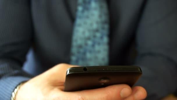 Detailní záběr na podnikatel procházení zpráv na jeho poslední generace smartphone.