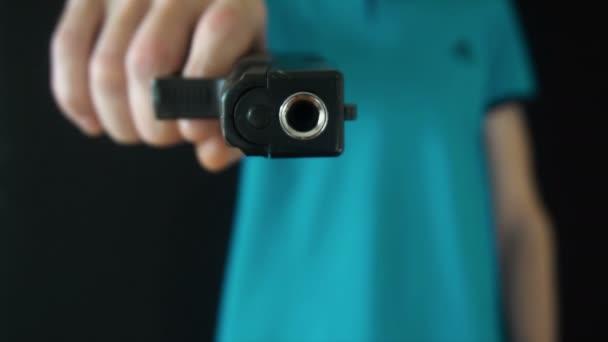 a fiatalember küld egy fekete pisztoly a kamera