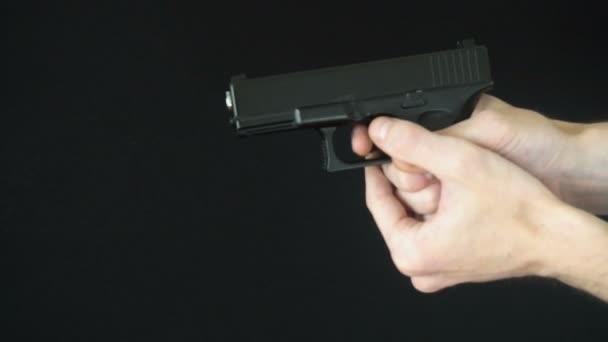 a fiatalember újratölti a fegyvert fekete