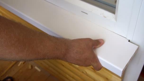 pracovník nainstaluje okenní parapet v lodžie