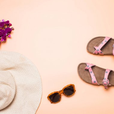 Straw hat, sandals and sunglasses on a pink background, square
