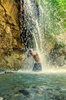Waterfall.  Young man refreshing in waterfall.