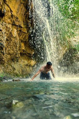 Waterfall.  Young man refreshing in waterfall.