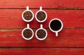 Káva. Šálky s kávou a kávová zrna na červeném pozadí dřevěná.