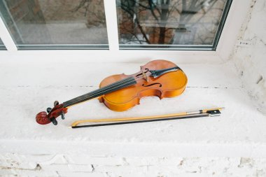 Violin and bow on window sill