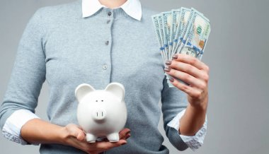 Savings concept. Woman holding piggy bank and bunch of money banknotes.