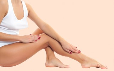 Woman legs with smooth skin after depilation on pastel background.
