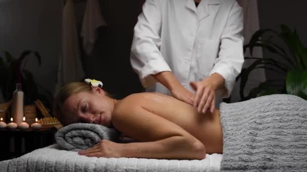 Gyönyörű fiatal nő kap vissza masszázs forró kövek spa szalon, masszőr csinál szakmai masszázs nő masszázs asztalon.