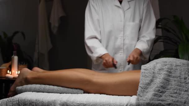 Gyönyörű fiatal nő kap lábak masszázs spa szalon, masszőr csinál szakmai masszázs nő masszázs asztalon.
