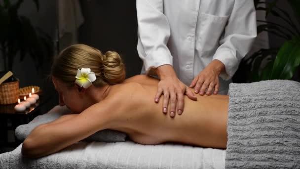 Krásná mladá žena se zavřenýma očima při masáži zad v lázeňském salonu, masérka při profesionální masáži ženy na masážním stole.