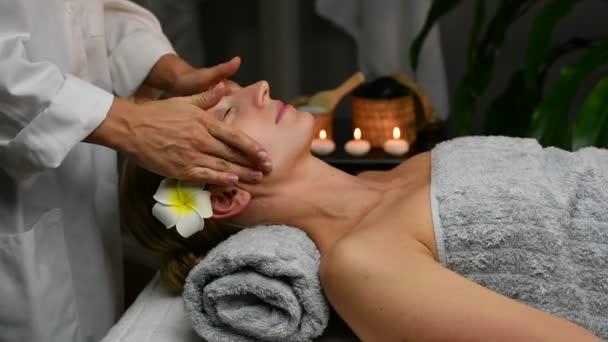Kosmetolog provádí profesionální masáž obličeje, žena podstupující kosmetické procedury a masáž obličeje v kosmetickém lázeňském centru.