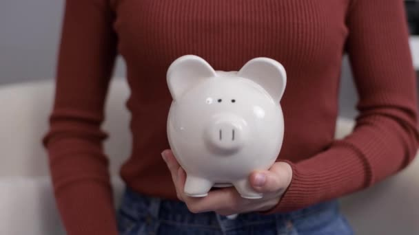 Žena, která vydělává úspory, dává peníze do prasátka. Žena dává mince do prasátka..