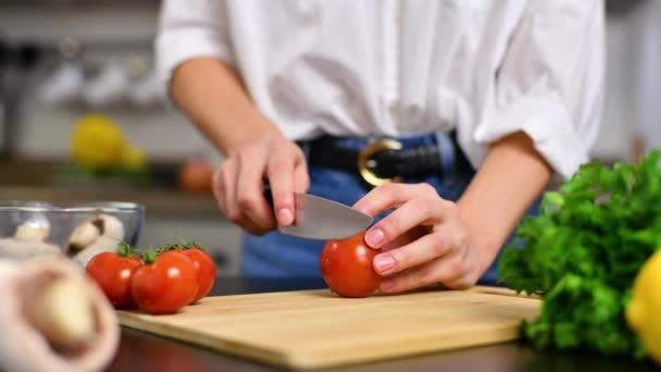 A nő lassított felvételen vágja fel a paradicsomot a konyhaasztalon. Friss zöldség salátához