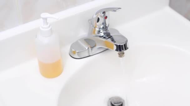 Voda tekoucí v umyvadle, pak ženská ruka vypne kohoutek v koupelně.