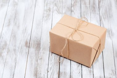 Gift boxes with kraft paper over wooden background.