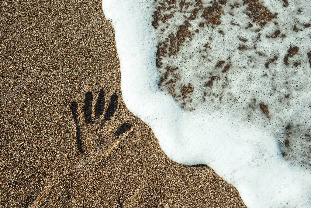 Print of the hand on sand.