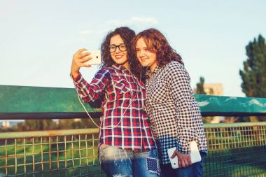 Two girls girlfriend take a selfie on smartphone and listening to music outdoors.