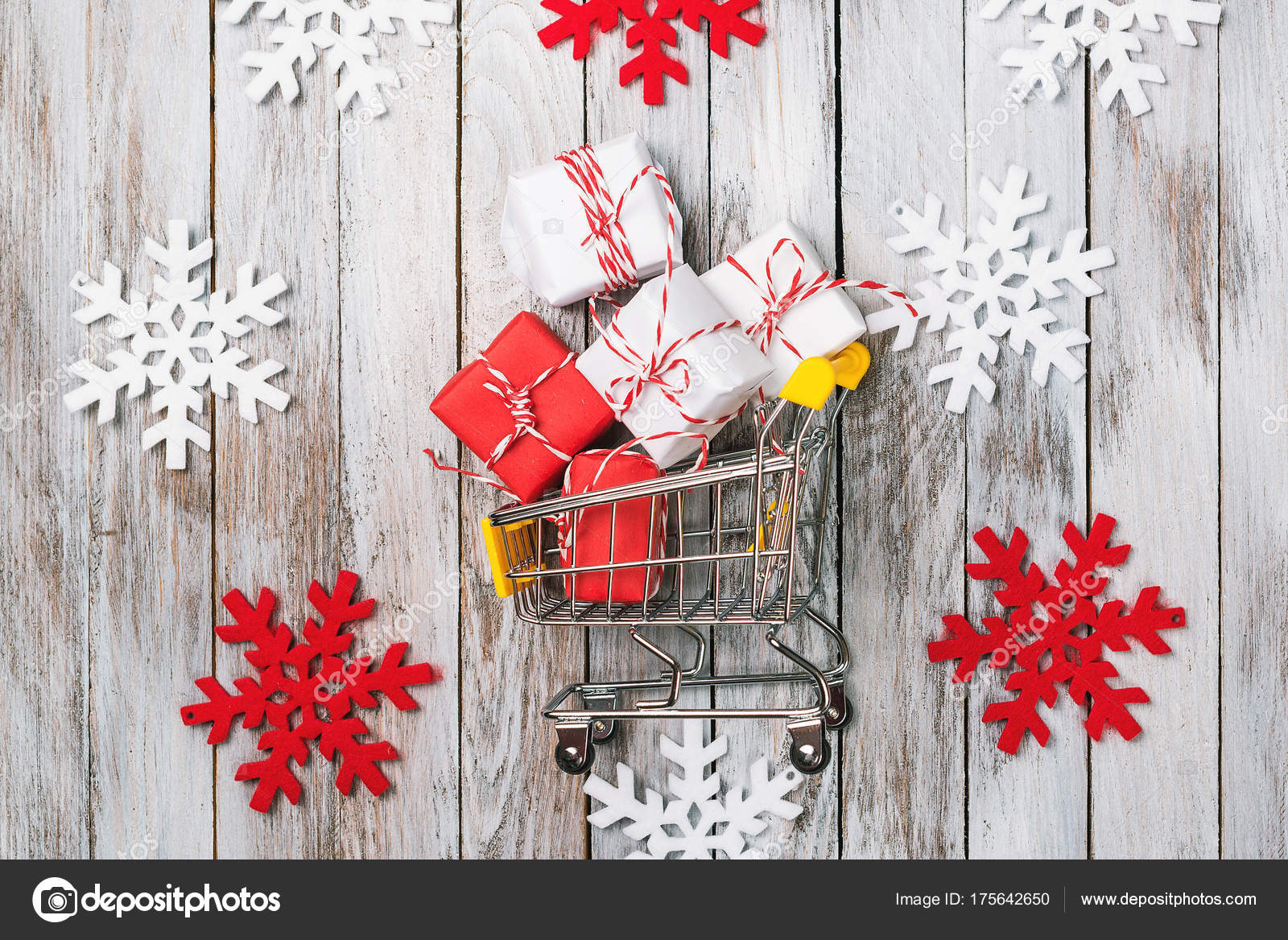 Christmas gift boxes in shopping cart on a wooden background with ...
