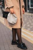 Módní model v módním barevném kabátě s černou kabelkou a moderními černými botami na městské ulici. Stylová dívka držící módní čepici. Dámská móda, podzimní styl