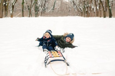 Happy brothers lying on snow outdoors. Kids having fun together in winter park. Happy and healthy childhood