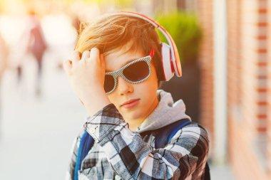 Stylish boy wearing sunglasses. Happy kid using headphone listening favorite music outdoors. Fashion, lifestyle and tecnology concept.