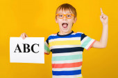 Excited happy little boy learning letters. Boy holds ABC card over yellow background. Speech therapist lessons.