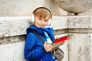 Cute young boy listening to music on tablet outdoors. Kid using wireless headphone. Stylish boy walking the street and enjoying music. People, technology and lifestyle. Handsome kid outside. Fashion.