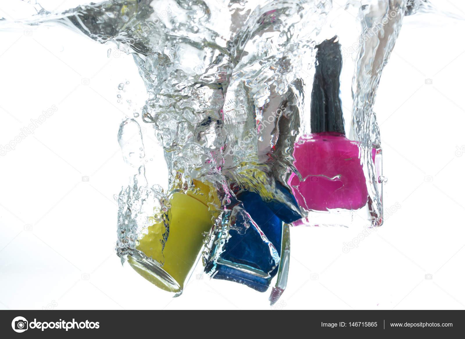Nagellack Flaschen ins Wasser fallen, auf weißem Hintergrund ...
