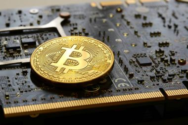 Florence, Italy - March 16, 2018: Cryptocurrency Phisical Gold Bitcoin over modern GAINWARD Nvidia GeForce GTX 670 Phantom Gaming graphics card. Mining equipment.