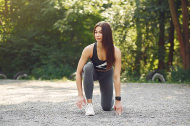 Sports girl in a black top training in a summer park