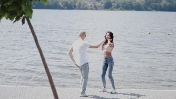 Couple dancing close to lake in park on summer day