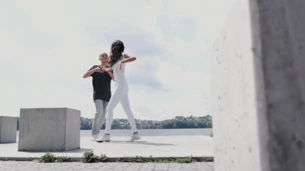 Active couple having dance training near lake