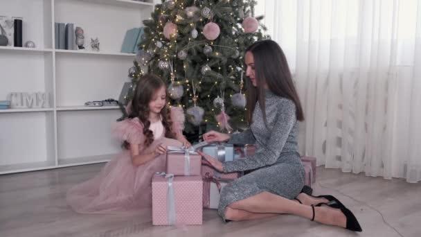 Mutter und Tochter in Kleidern beim Auspacken von Weihnachtsgeschenken