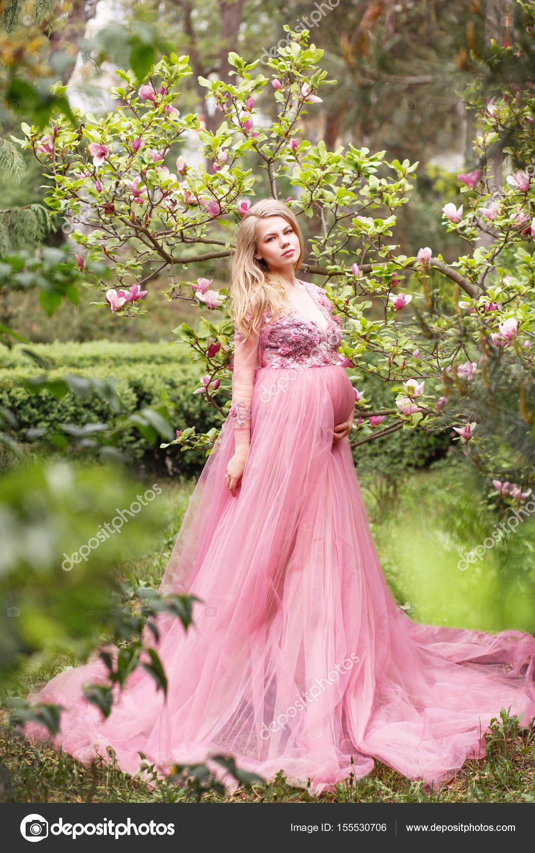 Mujer embarazada joven hermosa en un vestido rosa largo sexy de pie ...