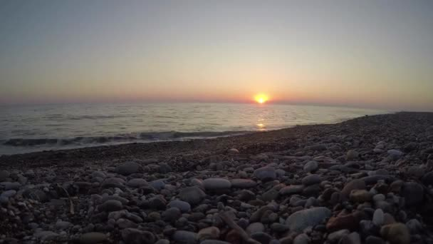 Timelapse of bright orange sun setting into the Black Sea. Sunset on a pebble beach
