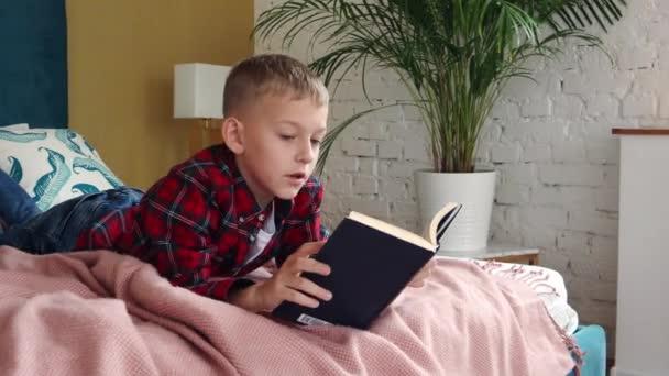 Mladý osmiletý chlapec ležící na posteli a čtoucí knihu.
