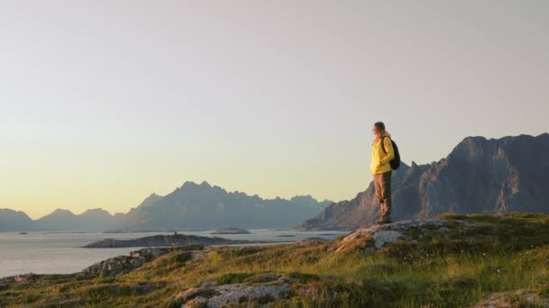 Woman traveler relaxing and enjoying the view of Norwegian landscape from a hill