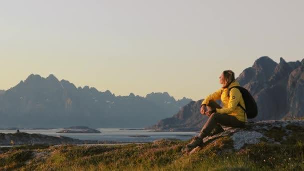 Žena cestovatel relaxační a těší pohled na norskou krajinu z kopce
