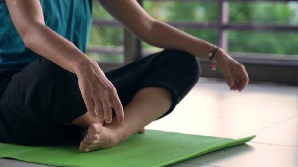 Detailní záběr ženy relaxující na podložce jógy ve studiu jógy