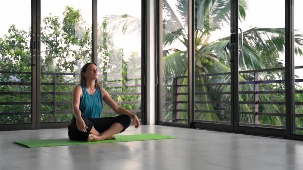 Mladá žena odpočívající na podložce jógy ve studiu jógy